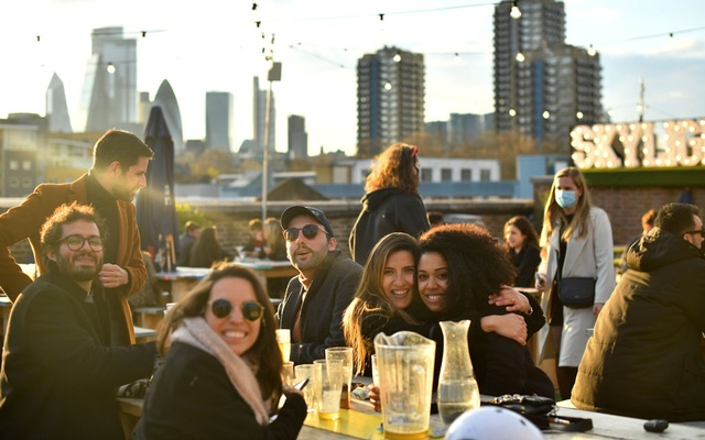 People enjoy the sun at the Skylight rooftop bar as the coronavirus disease (COVID-19) restrictions ease, in London, Britain April 12, 2021. Reuters