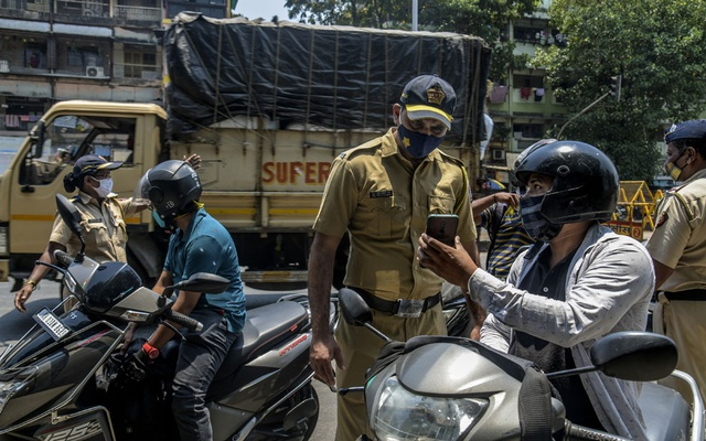 Law enforcement officers check credentials of people traveling in Mumbai, India, on Thursday, April 15, 2021, the first day of new lockdown due to the coronavirus pandemic. (Atul Loke/The New York Times)