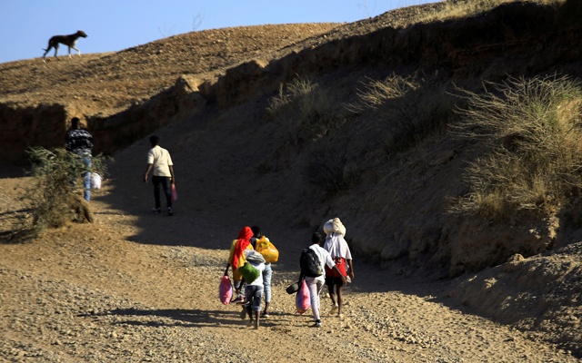 Ethiopians, who fled the ongoing fighting in Tigray region, carry their belongings after crossing the Setit River on the Sudan-Ethiopia border, in the eastern Kassala state, Sudan December 16, 2020. REUTERS