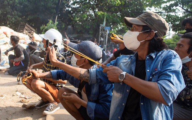 Men use slingshots as they crouch behind a barricade during a protest against the military coup, in Yangon, Myanmar March 28, 2021. REUTERS