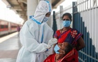 A healthcare worker in personal protective equipment (PPE) collects a swab sample from a woman, amidst the spread of the coronavirus disease (COVID-19), at a railway station in Mumbai, India, Apr 16, 2021. REUTERS