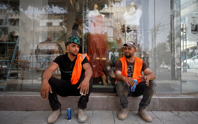 Labourers take a break as Israel rescinds the mandatory wearing of face masks outdoors in the latest return to relative normality, boosted by a mass-vaccination campaign against the coronavirus disease (COVID-19) pandemic, in Tel Aviv, Israel April 18, 2021. REUTERS