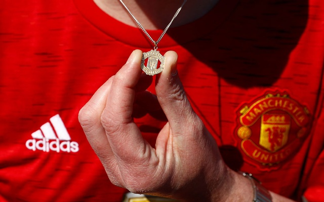 Soccer Football - A Manchester United fan holds their Manchester United logo necklace outside Old Trafford as twelve of Europe's top football clubs launch a breakaway Super League - Manchester, Britain - April 19, 2021 REUTERS/Jason Cairnduff