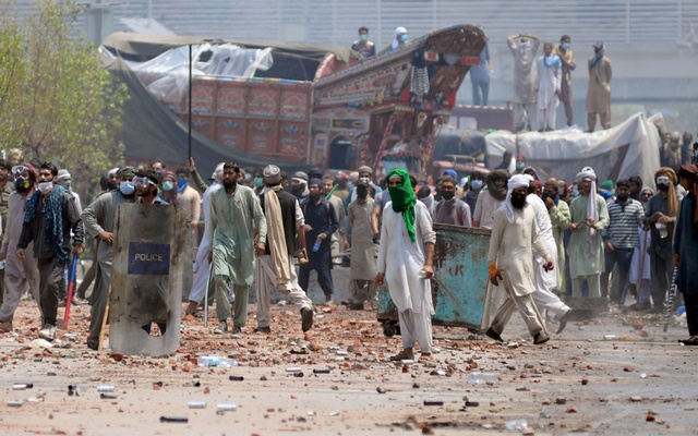 Supporters of the banned Islamist political party Tehrik-e-Labaik Pakistan (TLP) with sticks and stones block a road during a protest in Lahore, Pakistan Apr 18, 2021. REUTERS