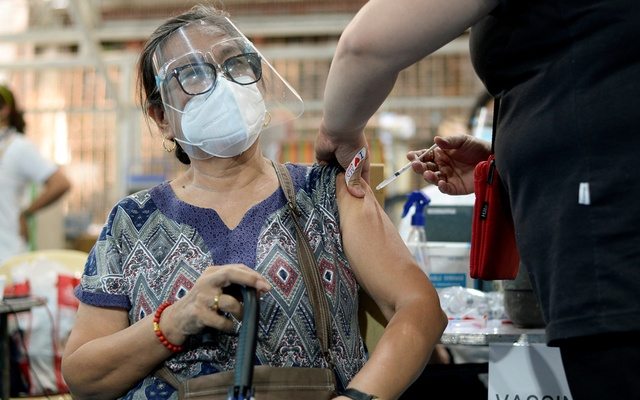 A senior citizen receives her first dose of AstraZeneca coronavirus disease (COVID-19) vaccine, at a covered court in Manila, Philippines, Mar 29, 2021. REUTERS