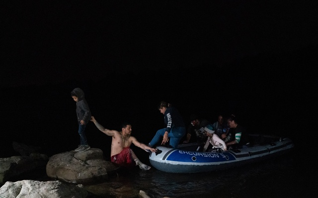 """A smuggler, or """"coyote,"""" helps migrants step ashore after crossing from Mexico at a narrow spot of the Rio Grande River near Roma, Texas, April 16, 2021. The New York Times"""