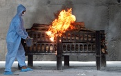 FILE PHOTO: A frontline worker in personal protective equipment (PPE) sprays a flammable liquid on a burning funeral pyre of a man who died from the coronavirus disease (COVID-19), at a crematorium on the outskirts of Mumbai India, April 15, 2021. REUTERS/Francis Mascarenhas/File Photo