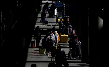 Travellers walk through a pick-up area in the arrivals section at Seattle-Tacoma International Airport in SeaTac, Washington, US April 12, 2021. REUTERS