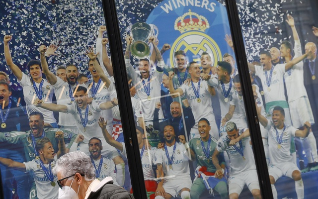 Twelve of Europe's top football clubs launch a breakaway Super League - Madrid, Spain - April 20, 2021 A woman wearing a facemask walks past a picture of Real Madrid celebrating with the Champions League trophy as twelve of Europe's top football clubs launch a breakaway REUTERS