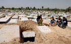 Palestinians wait to bury the body of their relative, who died after contracting the coronavirus disease (COVID-19), at a cemetery, east of Gaza City April 20, 2021. REUTERS