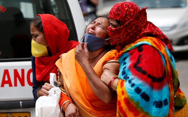 FILE PHOTO: A woman is consoled after her husband died due to the coronavirus disease (COVID-19) outside the mortuary of a COVID-19 hospital in Ahmedabad, India, April 20, 2021. REUTERS/Amit Dave/File Photo