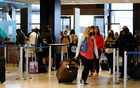 Travellers stand at check-in lines at Seattle-Tacoma International Airport in SeaTac, Washington, US April 12, 2021. REUTERS