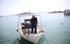 A fisherman prepares to moor his boat at the port, amid the coronavirus disease (COVID-19) pandemic, on the island of Halki, Greece, April 13, 2021. REUTERS
