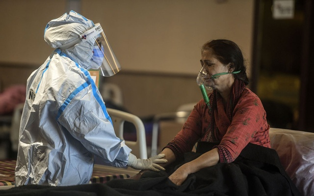 A health care worker assists a patient with COVID-19 at a hospital in Delhi, India, April 23, 2021. India's coronavirus second wave is rapidly sliding into a devastating crisis, with hospitals unbearably full, oxygen supplies running low, desperate people dying in line waiting to see doctors — and mounting evidence that the actual death toll is far higher than officially reported. (Atul Loke/The New York Times)