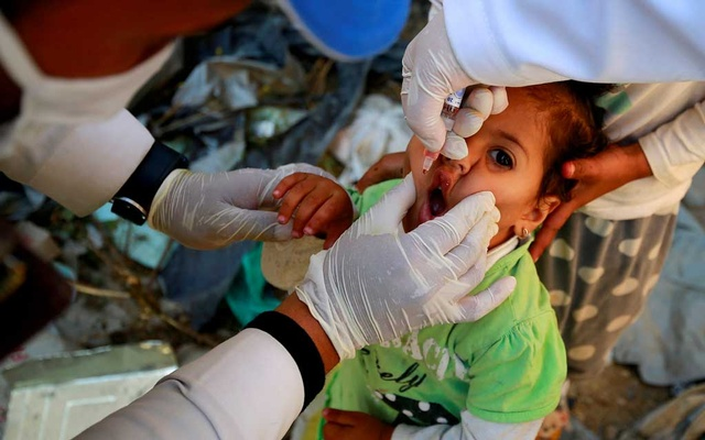 FILE PHOTO: A girl receives a polio vaccine during a three-day immunisation campaign in Sanaa, Yemen November 29, 2020. REUTERS/Nusaibah Almuaalemi/File Photo