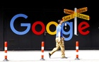 A man walks past a logo of Alphabet Inc's Google in front of at an office building in Zurich, Switzerland July 1, 2020. REUTERS