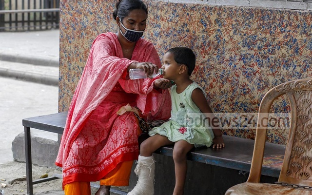 Nasima Begum came to Pangu Hospital in Dhaka from Savar for the treatment of her minor daughter Roza Moni. Nasima had to walk carrying Roza from the hospital in Sher-e-Bangla Nagar to Gabtoli while returning home on Wednesday, Apr 28, 2021 as there was no public transport amid a coronavirus lockdown. The mother fed the girl outside Gabtoli Bus Terminal before resuming the journey to Savar on foot. Photo: Mahmud Zaman Ovi