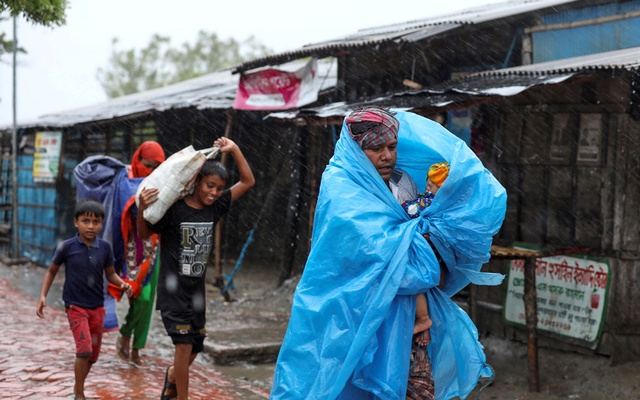 People make their way to a safer place before the cyclone Amphan makes its landfall in Gabura outskirts of Satkhira district, Bangladesh May 20, 2020. REUTERS