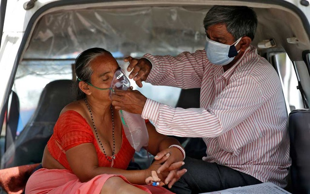 Spread of the coronavirus disease (COVID-19) in Ahmedabad The husband of Nanduba Chavda adjusts his wife's oxygen mask as they wait in a car to enter a COVID-19 hospital for treatment, amidst the spread of the coronavirus disease (COVID-19) in Ahmedabad, India, April 28, 2021. REUTERS