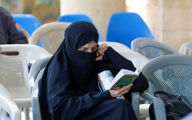 Ruqaiya, 70, reads a religious book while waiting to receive her dose of coronavirus disease (COVID-19) vaccine, at a vaccination centre in Karachi, Pakistan April 28, 2021. REUTERS/Akhtar Soomro