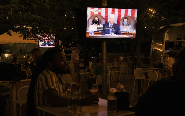 Televisions at Dacha Beer Garden in Washington show President Joe Biden addressing a joint session of Congress at the Capitol, as Vice President Kamala Harris and Speaker of the House Nancy Pelosi (D-Calif.) look on, April 28, 2021. (Alyssa Schukar/The New York Times)