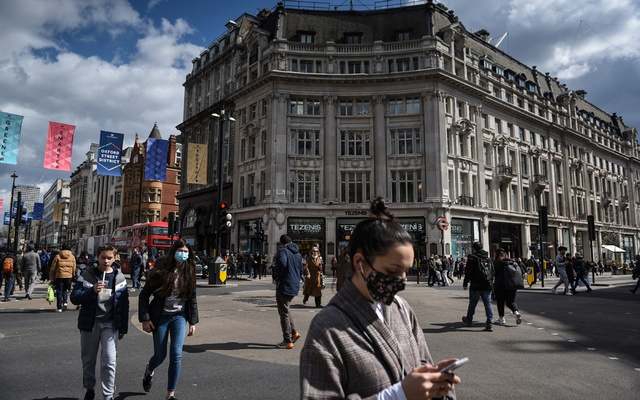People return to Oxford Circus in London as retail shops open and England begins to lift its third Coronavirus lockdown restrictions, on Monday, April 12, 2021, following a COVID-19 lockdown