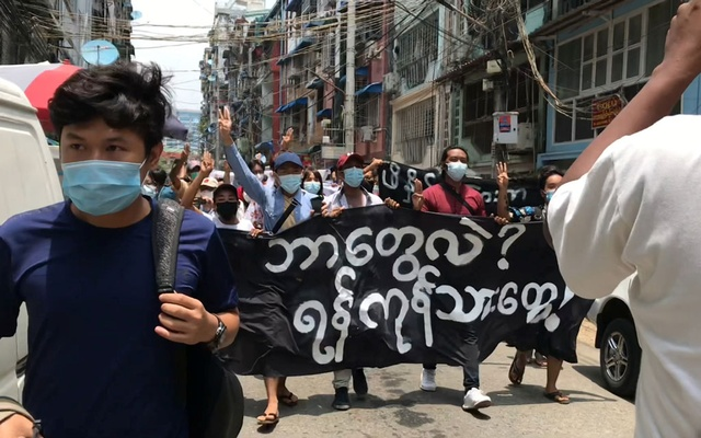 Demonstrators carry a banner reading