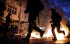 Police officers run past a fire during a left-wing May Day demonstration, as the spread of the coronavirus disease (COVID-19) continues in Berlin, Germany, May 1, 2021. REUTERS