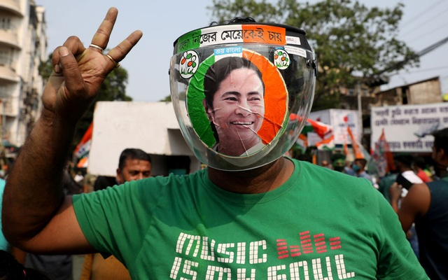 A supporter of the Chief Minister of West Bengal state and the Chief of Trinamool Congress (TMC) Mamata Banerjee, wearing a face shield with her image on it, gestures during celebrations after the initial poll results, amid the spread of coronavirus disease (COVID-19), in Kolkata, India, May 2, 2021. Reuters