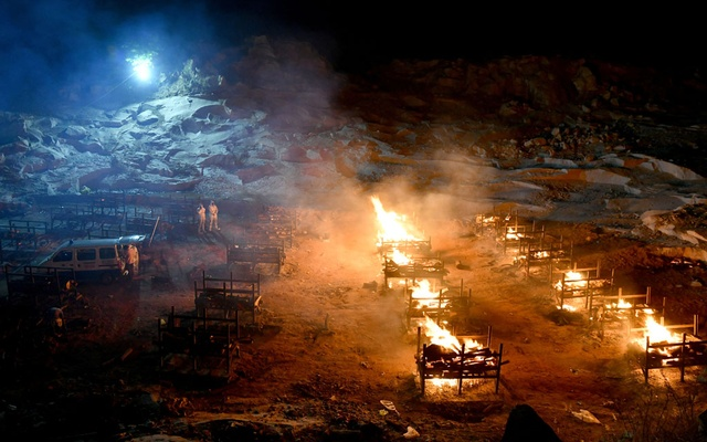 Volunteers stand next to burning pyres of persons who died due to the coronavirus disease (COVID-19), at a crematorium ground in Giddenahalli village on the outskirts of Bengaluru, India, May 2, 2021. Reuters