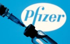 A vial and syringe are seen in front of a displayed Pfizer logo in this illustration taken January 11, 2021. REUTERS