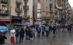 People in line for food coupons outside a social protection office in Barcelona, Spain, on March 30, 2020. While the U.S. has become a symbol of fecklessness and discord in the face of a grave emergency, Europe has generally protected workers' livelihoods and gotten a handle on the spread of the coronavirus, enabling many economies to reopen. (Samuel Aranda/The New York Times)