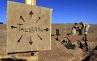 FILE PHOTO: US Marines from Charlie 1/1 of the 15th MEU (Marine Expeditionary Unit) fill sandbags around their light mortar position on the frontlines of a US Marine Corps base, near a cardboard sign reminding everyone that Taliban forces could be anywhere and everywhere, in southern Afghanistan December 1, 2001. REUTERS/Jim Hollander/File Photo