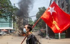 FILE PHOTO: A man holds a National League for Democracy (NLD) flag during a protest against the military coup, in Yangon, Myanmar March 27, 2021. REUTERS/Stringer/File Photo