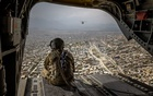 An Army soldier aboard a Chinook helicopter looks out over Kabul, Afghanistan, on Sunday, May 2, 2021. Afghan ground commanders are pleading for more help from American warplanes. Jim Huylebroek/The New York Times