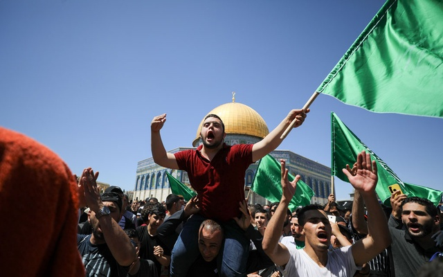 People hold Hamas flags as Palestinians gather after performing the last Friday of Ramadan to protest over the possible eviction of several Palestinian families from homes on land claimed by Jewish settlers in the Sheikh Jarrah neighbourhood, in Jerusalem's Old City, May 7, 2021. REUTERS