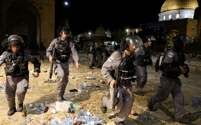 Israeli police run during clashes with Palestinians at the compound that houses Al-Aqsa Mosque, known to Muslims as Noble Sanctuary and to Jews as Temple Mount, amid tension over the possible eviction of several Palestinian families from homes on land claimed by Jewish settlers in the Sheikh Jarrah neighbourhood, in Jerusalem's Old City, May 7, 2021. REUTERS