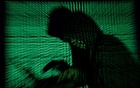 A hooded man holds a laptop computer as cyber code is projected on him in this illustration picture taken on May 13, 2017. Top US fuel pipeline operator Colonial Pipeline has shut its entire network after a cyber attack, the company said on Friday. REUTERS