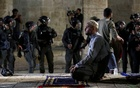 A Palestinian man prays as Israeli police gather during clashes at the compound that houses Al-Aqsa Mosque, known to Muslims as Noble Sanctuary and to Jews as Temple Mount, amid tension over the possible eviction of several Palestinian families from homes on land claimed by Jewish settlers in the Sheikh Jarrah neighbourhood, in Jerusalem's Old City, May 7, 2021. REUTERS