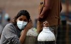 A woman holds on to the oxygen cylinders for a patient after refiling them at a factory, amidst the spread of coronavirus disease (COVID-19) surge as India's outbreak spreads across South Asia, in Kathmandu, Nepal May 9, 2021. REUTERS