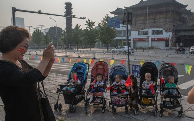 Babies hold Chinese flags in their strollers in Beijing, Oct. 1, 2019, as China celebrates 70 years of Communist Party rule. The number of babies born in China last year fell to a nearly six-decade low, exacerbating a looming demographic crisis that is set to reshape the world's most populous nation and threaten its economic vitality. The New York Times