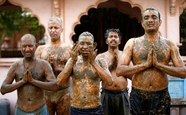 People pray after applying cow dung on their bodies during