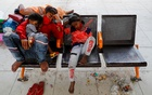 A migrant worker and his children sleep at a bus station as they wait to return to their village, after Delhi government ordered a six-day lockdown to limit the spread of the coronavirus disease (COVID-19), in Ghaziabad on the outskirts of New Delhi, India, April 20, 2021. Reuters