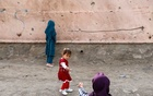 Children stand next to a damaged wall at the site of a car bomb blast that targeted schoolgirls in Kabul, Afghanistan May 10, 2021. REUTERS