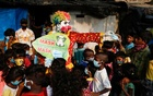 A man dressed as a clown distributes face masks to children in a slum area, amidst the coronavirus disease (COVID-19) outbreak, in Mumbai, India, May 3, 2021. REUTERS/Francis Mascarenhas