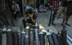 People wait in New Delhi for oxygen cylinders to be refilled on May 3, 2021. Vaccine shortages, porous borders and fleeing migrant workers have nearby countries fearing that they will share India's fate. (Atul Loke/The New York Times)