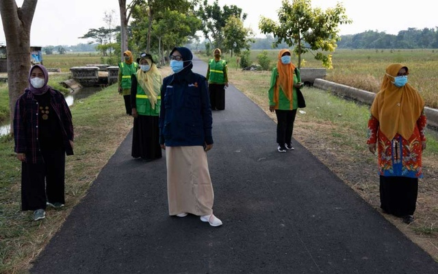 National and regional leaders of 'Aisyiyah's environmental chapter stand between trees the group planted in Sukoharjo, Central Java province, Indonesia on May 5, 2021. Thomson Reuters Foundation/Harry Jacques
