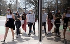 A group of people walk wearing protective masks head to a restaurant as coronavirus disease (COVID-19) restrictions are eased in Ann Arbor, Michigan, US, April 4, 2021. REUTERS