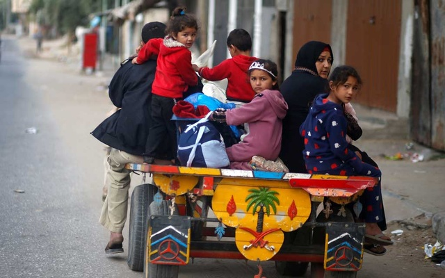 Palestinians ride on a donkey-drawn cart as they flee their homes during Israeli air and artillery strikes, in the northern Gaza Strip May 14, 2021. REUTERS