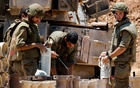 Israeli soldiers check artillery shells in an area near the border with Gaza, in southern Israel May 13, 2021. REUTERS